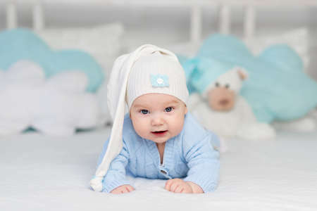 Photo pour a baby on a bed in a hood goes to bed or wakes up in the morning. Textiles and bedding for children. Newborn baby with a toy bear - image libre de droit
