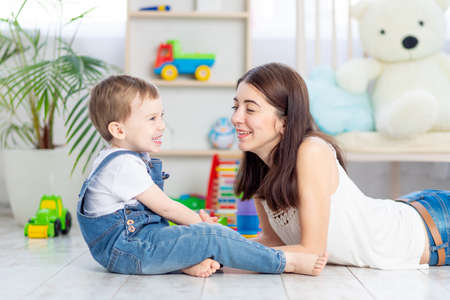 Photo pour the mother talks to the baby boy or plays at home with educational toys in the children's room. A happy, loving family. - image libre de droit