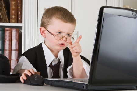 Four year old boss playing director and looking at his computer screen