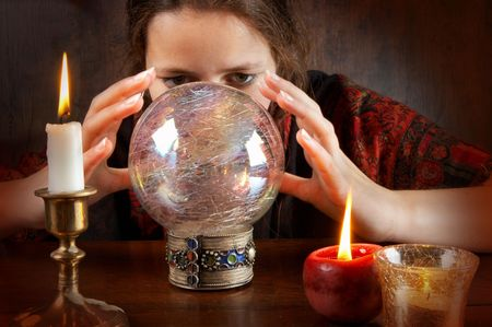 Young fortune teller in a red scarf working with her crystal ball