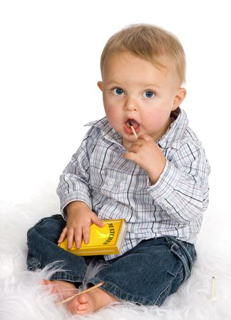 Curious baby playing a dangerous game with matches