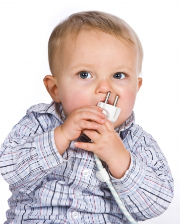 Curious baby playing a dangerous game with an electric plug
