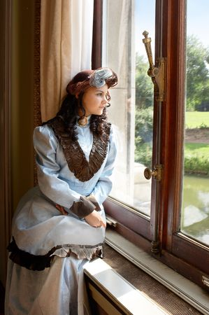 Vintage portrait of a victorian lady standing by a castle window.Shot in the antique castle Den Brandt in Antwerp, Belgium (with signed property release for the Castle interiors).