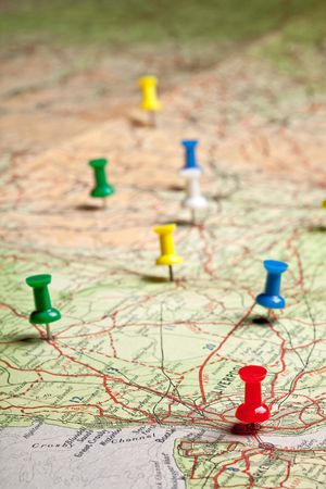 Colored pushpins on a road map of a tourist