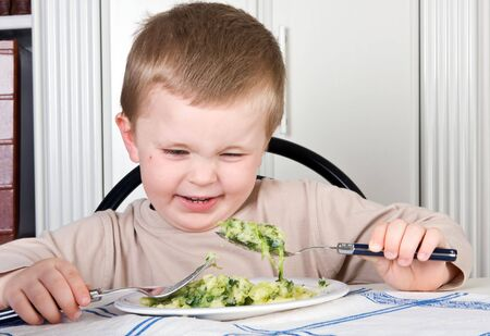Four year old boy looking with disgust at the food on his plate