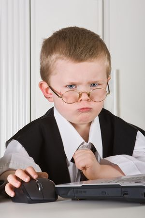 Four year old boy playing angry director in his office