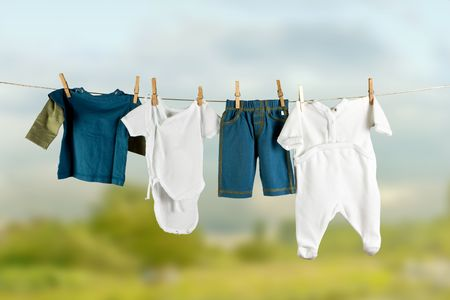 White and colored baby laundry hanging on a clothesline