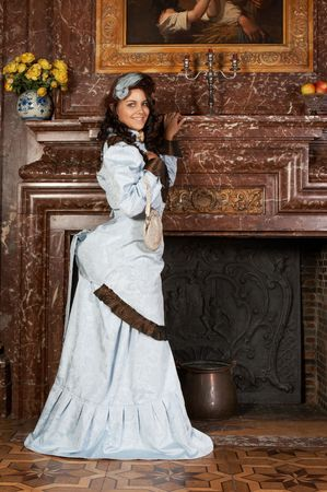 Portrait of a beautiful young victorian lady in a genuine bustle dress.Shot in the antique castle Den Brandt in Antwerp, Belgium (with signed property release for the Castle interiors).