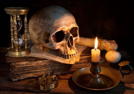 Vintage skull on antique book with candle and hourglass