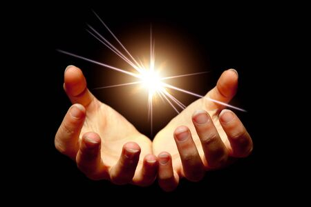 Female hands holding a brilliant star in the dark