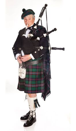 Scottish highlander wearing kilt and playing bagpipes