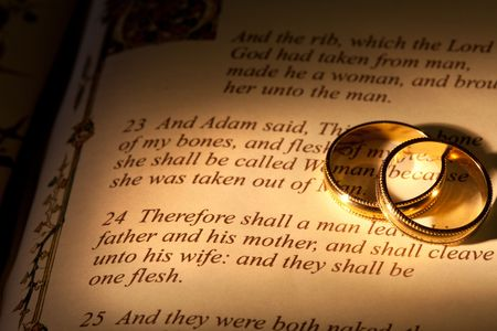 Rings and Bible with Genesis text of Adam and Eve, a typical wedding text - the book illustration is copied from a 400 years old bible.