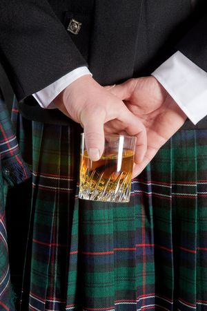 Scotsman holding his glass of whisky behind is kilt
