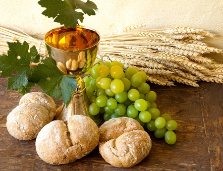 Grapes and holy bread next to a golden chalice with wine