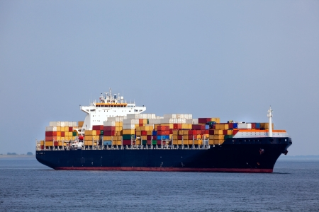 Huge container ship passing - all brand names removed from every container