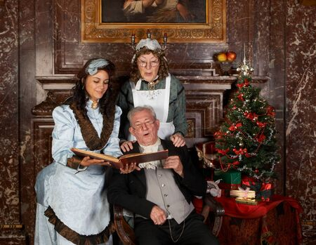 Vintage christmas scene of a victorian family singing christmas carols.