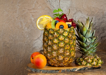 Pineapple filled with colorful assorted fruit salad
