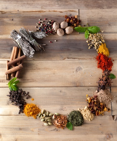 Beautiful circle of colorful spices and herbs on a wooden table