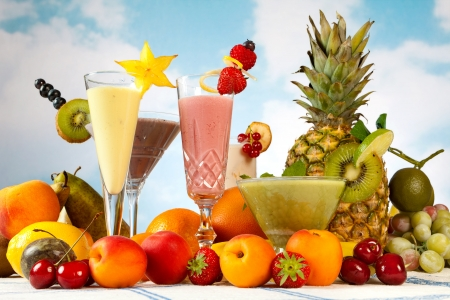 Milkshake or smoothie table with lots of summer fruits