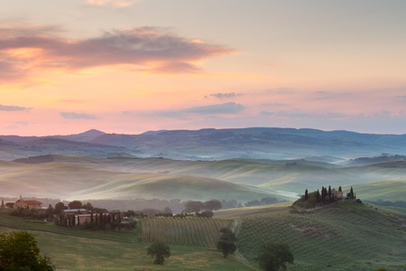 Misty morning in the Tuscan hills at San Quirico d'Orcia with view on Belvedere villa