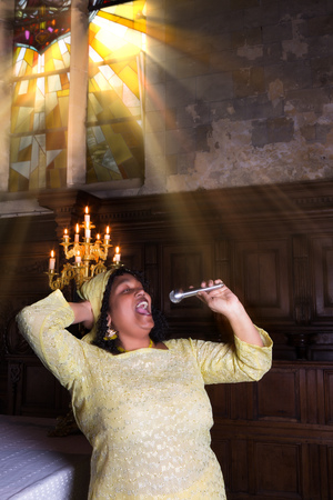 Gospel singer during mass with sunshine through the stained glass windows of a medieval church