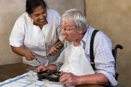 Nurse in old people's home trying to make a patient eat his dinner