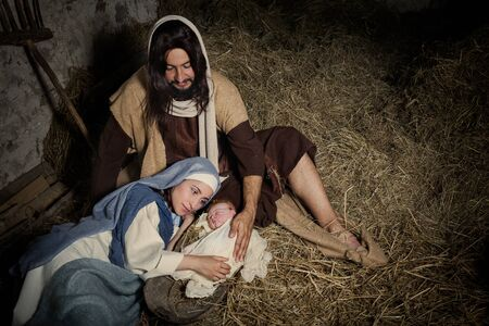 Photo pour Live Christmas nativity scene in an old barn - Reenactment play with authentic costumes.  The baby is a (property released) doll. - image libre de droit