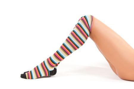 Shot of woman legs in multicolored stockings sitting onthe floor