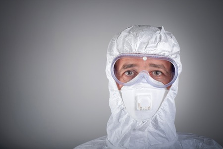 Scientist in protective wear, glasses, respirator