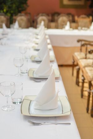 Photo for Long served table with plates, glasses, napkins and chairs - Royalty Free Image