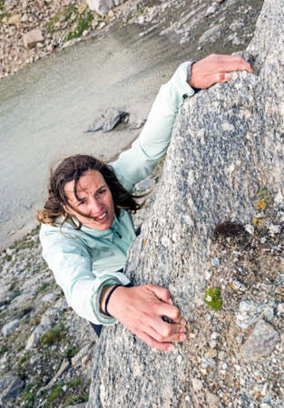 Female climber desperately griping a hold above a lake.
