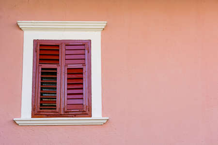 Detail of olf wooden window with closed shutters.