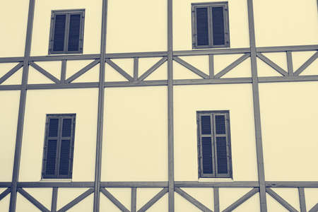 Timber framed facade of old building with wooden windows.