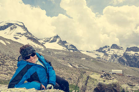 Photo for Female mountaineer resting on a rock surrounded by spectacular mountain views. Active lifestyle. - Royalty Free Image