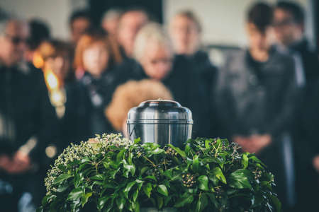Photo pour A metal urn with ashes of a dead person on a funeral, with people mourning in the background on a memorial service. Sad grieving moment at the end of a life. Last farewell to a person in an urn. - image libre de droit