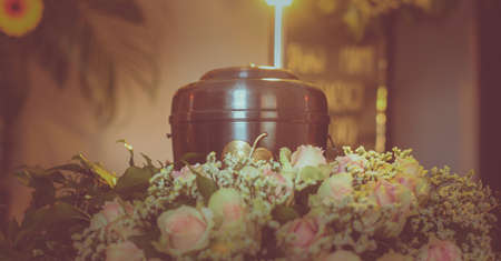 Photo pour A metal urn with ashes of a dead person on a funeral with noone around on a memorial service. Sad grieving moment at the end of a life. Last farewell to a person in an urn. - image libre de droit