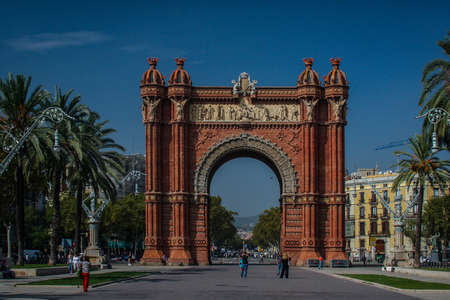 Photo pour Arc de triomphe or arch of triumph in Barcelona, Spain in a clear sunny day with only a few tourists lingering by. Frontal shot of Arc de Triomphe in Barcelona. - image libre de droit