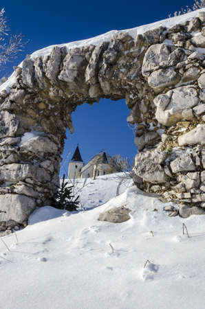 Through ruin view on St  Ursula church on top of the Plesivec mountain, highest elevation church in Slovenia at 1696m above sea level
