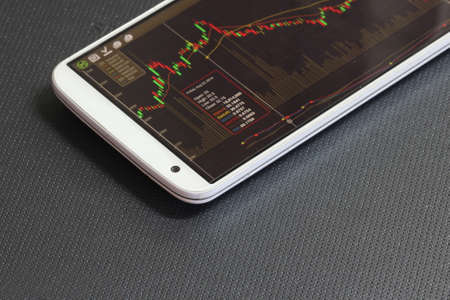 smartphone and stock chart investment trading background
