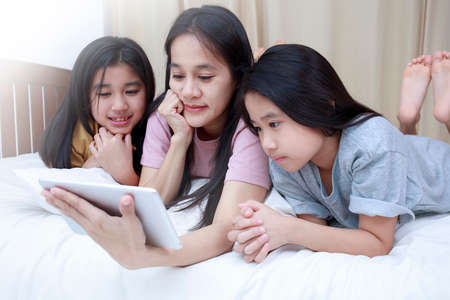 Photo pour Happy Asian family enjoy and relax on bed in bedroom. mother and daughters enjoy using tablet together on bed.  Family concept. - image libre de droit