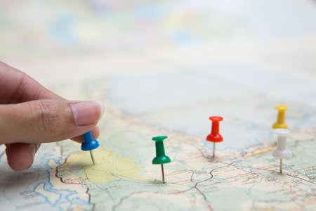 Photo pour Selective focus of hand holding a pin on map background - image libre de droit