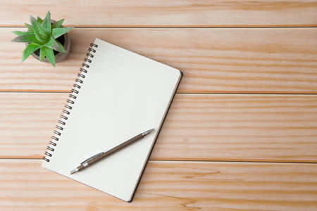 Photo for Top view of Notebooks, pens, glasses, cactus on wooden desks with sunlight and copy space - Royalty Free Image