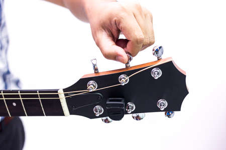 Person tuning a guitar over white background in selective focus