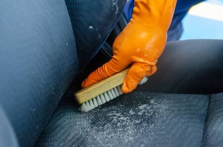 Photo pour Men wearing gloves to catch the car seat cleaning brush - image libre de droit