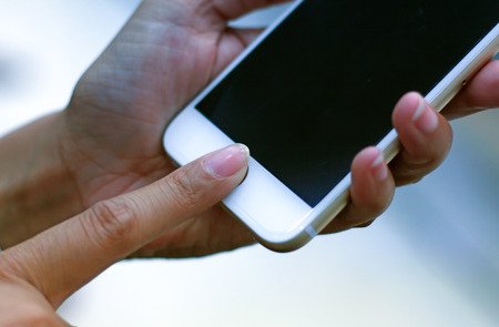 Women are scanned fingerprint or touch id to activate Smartphone.