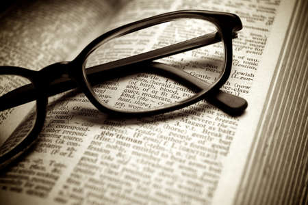 Close-up of old dictionary and black glasses
