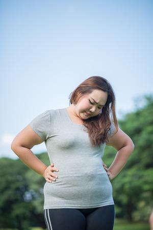 beautiful fat woman check her paunch in the garden