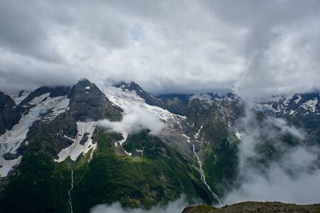 Photo pour Glacier and creek on a ridge in the clouds and fog. Dombay, Russia - image libre de droit