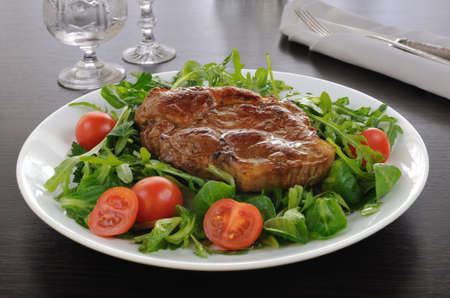 Grilled steak with bacon salad of arugula