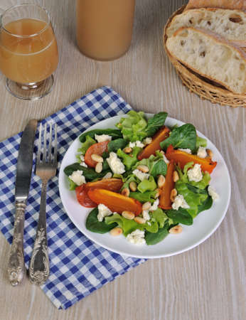 Fresh salad mix with persimmons, feta cheese and peanuts